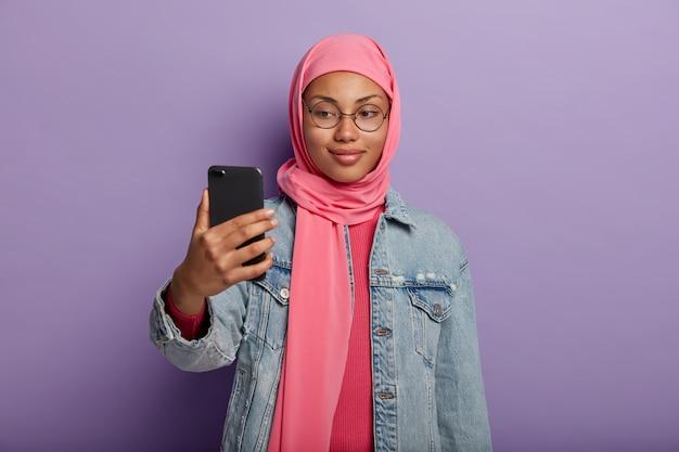 Atraente mulher muçulmana com sorrisinho, tira foto de si mesma via smartphone, vestida com roupas tradicionais segundo crenças religiosas.