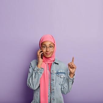 Atraente mulher muçulmana fala com a operadora sobre tarifas, segura um celular moderno, aponta com o dedo indicador para o espaço em branco acima, vestida com um lenço rosa, isolado sobre a parede roxa.