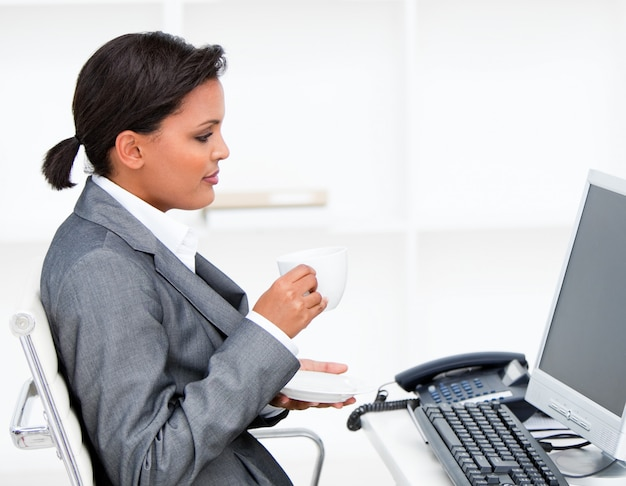 Atraente, mulher negócios, bebendo, coffe, enquanto, trabalhando, computador