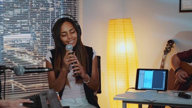 Atraente mulher negra com olhos fechados emocionalmente cantando música no microfone e gesticulando