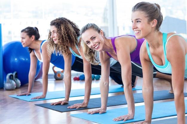 Atraente, mulheres, fazendo, prancha, pose, ligado, esteira exercício, em, centro aptidão