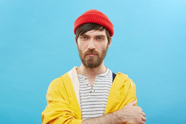 Atraente na moda jovem com barba usando chapéu vermelho da moda e capa de chuva amarela, mantendo os braços cruzados, olhando sério e confiante. pessoas, estilo e moda