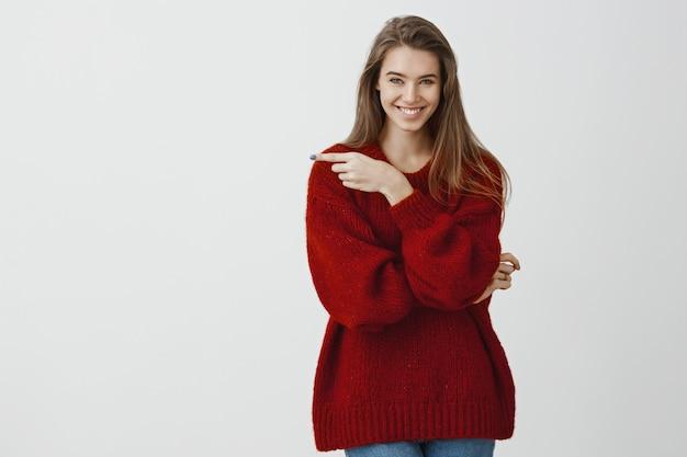 Atraente namorada criativa tem uma idéia interessante. prazer bem sucedida mulher romântica na camisola solta na moda, apontando para a esquerda com o dedo indicador e sorrindo amplamente, em pé confiante sobre parede cinza