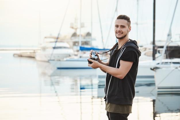 Atraente namorado focado em seu hobby durante passeio com a namorada. retrato de cara em pé no porto perto de iates, segurando a câmera, olhando de lado enquanto procurava por grande tiro.