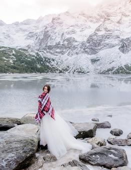 Atraente noiva coberta com manta está de pé sobre a rocha perto do lago congelado, rodeado por montanhas