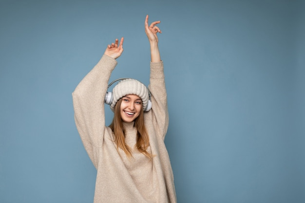 Atraente positiva sorridente jovem loira vestindo um suéter bege de inverno e um chapéu isolado