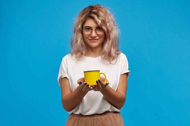 Atraente secretária jovem e simpática, vestindo camiseta branca e óculos, posando na parede azul com um copo amarelo nas mãos, oferecendo chá ou café recém-feito
