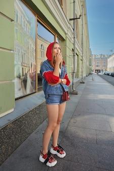 Atraente senhora branca em shorts, moletom e sapatos plarform ao ar livre.