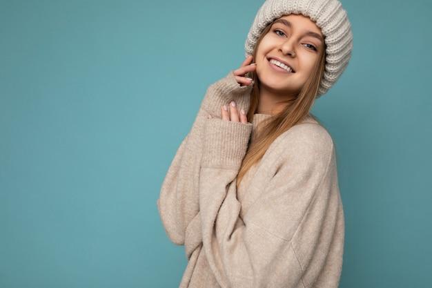 Atraente sorridente jovem loira escura de pé isolada sobre uma parede de fundo colorido, usando uma roupa elegante do dia a dia, mostrando emoções faciais, olhando para a câmera