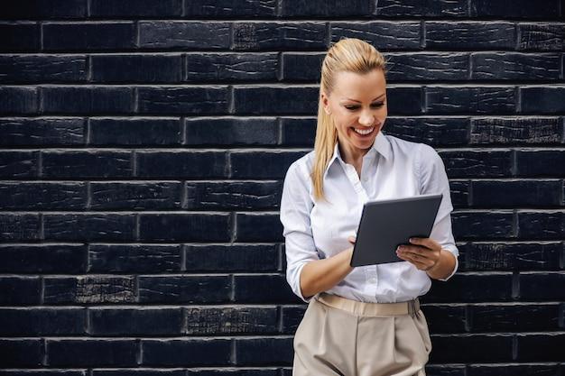 Atraente sorridente loira elegante empresária em frente a parede de tijolos e usando o tablet.