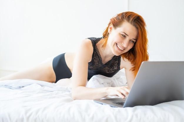 Atraente sorridente mulher ruiva de meia-idade deitada na cama usando um laptop em um quarto bem iluminado