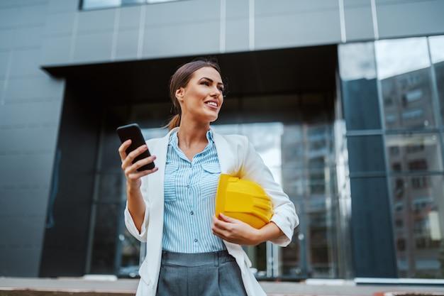 Atraente sorridente positiva elegante arquiteta feminina em frente a sua empresa com capacete sob a axila e o celular na mão e esperando os construtores chegarem.