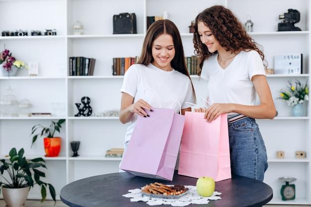 Atraentes, garotas de compras desembalam suas malas em casa