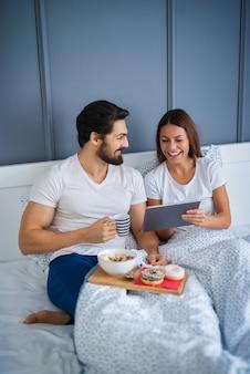 Atraentes jovens amantes felizes tomando café da manhã na cama juntos e lendo notícias de um tablet em casa ou no hotel.