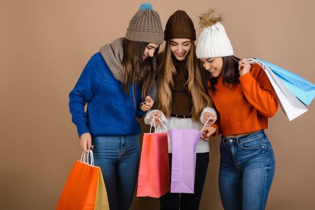 Atraentes, meninas jovens têm sacolas de compras nas mãos, aproveite as compras de natal
