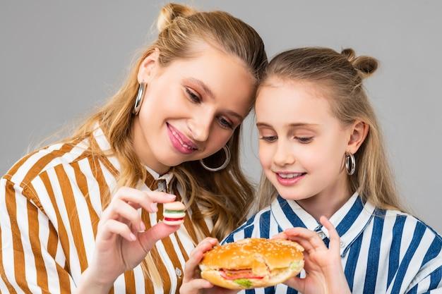 Atrair garotas bonitas e positivas comparando diferentes tamanhos de hambúrgueres enquanto ficam perto umas das outras