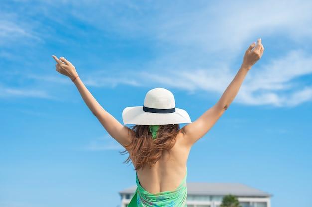 Atrás da mulher do curso com chapéu branco está relaxando na praia e no céu azul