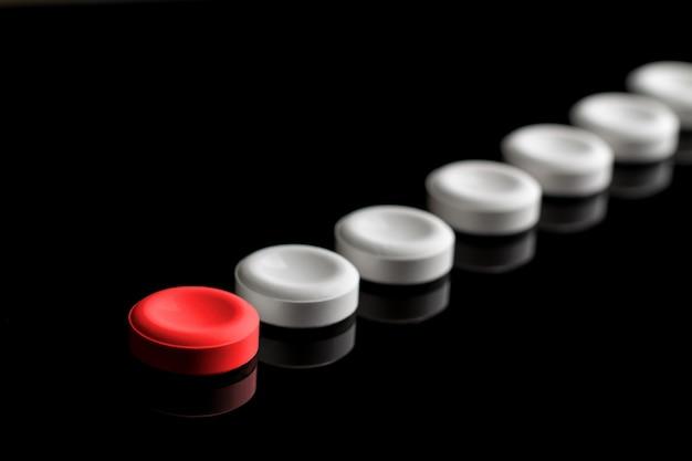 Atrás da pílula vermelha estão alinhados comprimidos brancos. conceito de liderança e recursos.