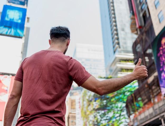 Atrás de um jovem mostrando o sinal de ok