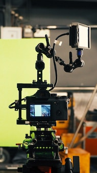 Atrás de uma câmera de vídeo e uma tela verde para filmes ou produção de filmes e equipamentos no grande estúdio.