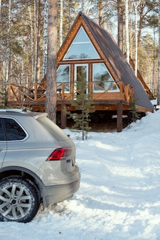 Atrás do carro, de cor prata, parado em um monte de neve na frente da câmera, no fundo de uma casa de campo na floresta, no fim de semana de inverno