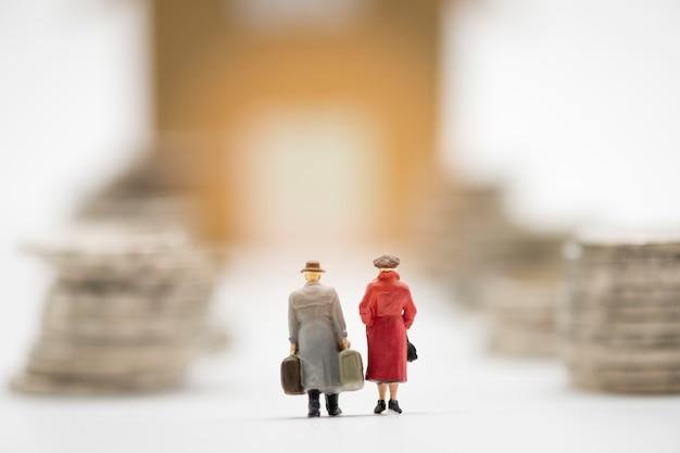 Atrás do homem e da mulher diminutos a mão modelo carreg a mala de viagem e a caminhada através das moedas que empilham para o movimento à casa nova.