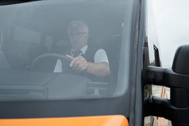 Atrás do pára-brisa, um motorista de ônibus caucasiano idoso de óculos sentado ao volante