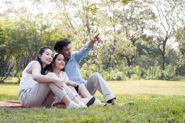Atrás pais e filhos estão brincando no tapete do parque.