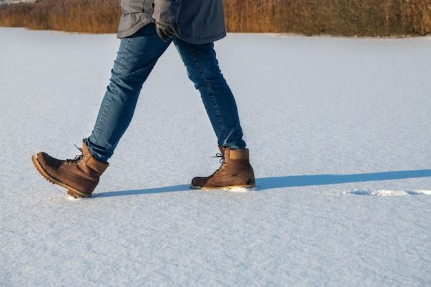 Atrasos femininos em botas andando na neve fresca no inverno. closeup de sapatos de inverno.