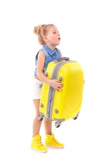 Atrativa menina bonitinha na camisa azul, calção branco e óculos de sol segurar a mala amarela
