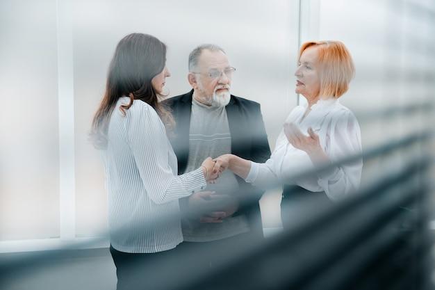 Através das cortinas, a senhora de negócios cumprimentando seu parceiro de negócios