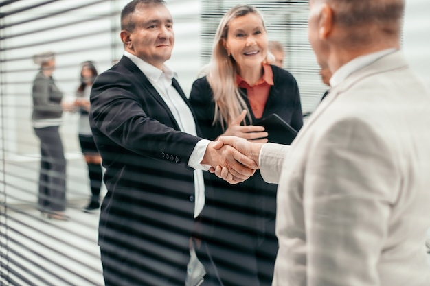 Através das cortinas, um empresário encontra seu parceiro de negócios