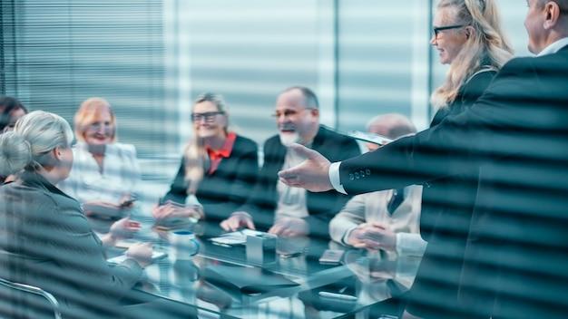 Através das cortinas. um grupo de funcionários aplaudindo em uma reunião de negócios. conceito de sucesso