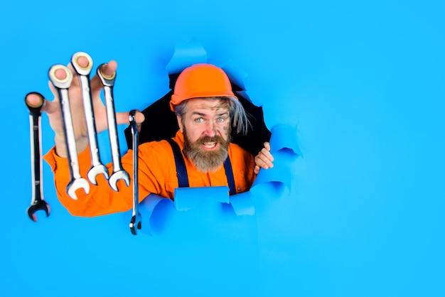 Através de papel, o trabalhador de publicidade segura chaves inglesas ferramentas de reparo de construção chave inglesa barbudo
