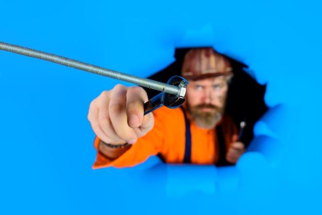 Através de papel publicitário, trabalhador em capacete segura chaves inglesas ferramentas de reparo chave inglesa barbudo