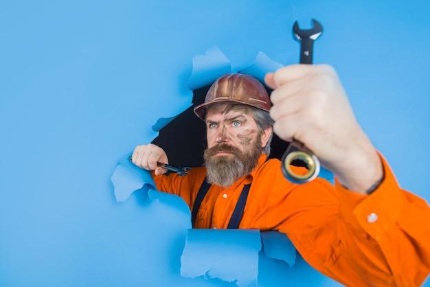Através do papel, o trabalhador de publicidade segura a chave inglesa, as ferramentas de reparo, o homem barbudo, através do papel