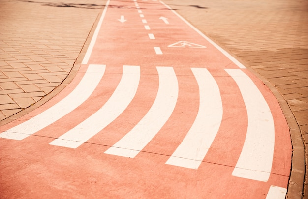 Atravessar a pé e sinal de seta direcional na ciclovia com pavimento
