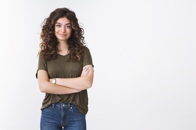 Atrevida, atraente, autônoma, autônoma, garota, armênia, com cabelo encaracolado, em pé, autoconfiante, braços cruzados no peito, sorrindo, determinada a realizar qualquer objetivo, pronta para resolver seu problema, fundo branco