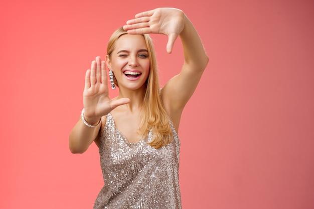 Atrevida e bonita mulher loira europeia criativa em um vestido prata brilhante piscando atrevido sorrindo confiante busca inspiração em torno de fazer moldura mão busca localização tirar foto legal, fundo vermelho