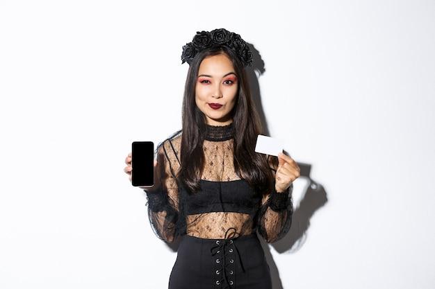 Atrevida e elegante jovem bruxa em um vestido de renda gótica e grinalda preta mostrando cartão de crédito e tela do celular