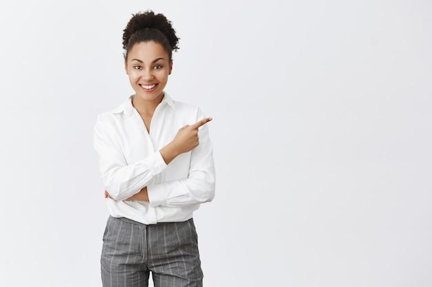 Atrevida empresária afro-americana mostrando o caminho, apontando para o canto superior direito