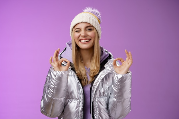 Atrevida garota loira atraente no casaco elegante ao ar livre com capuz chapéu mostrar nenhum problema ok gesto de perfeição satisfeito de boa qualidade do hotel sorrindo amplamente piscando a câmera atrevida, aproveitando as férias.