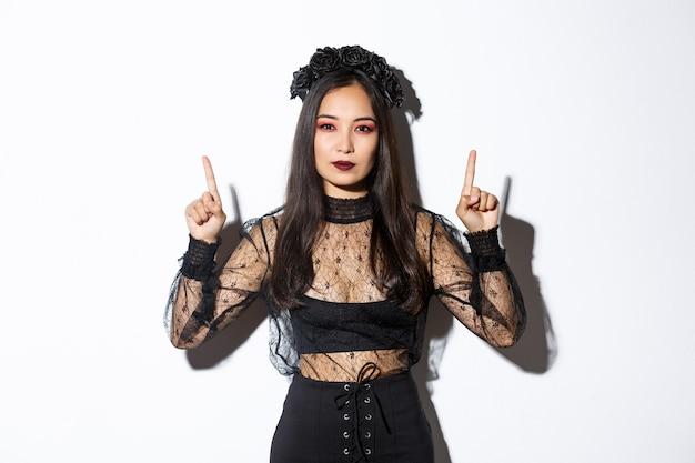 Atrevida linda mulher asiática em vestido gótico preto, vestindo fantasia de bruxa para o halloween e apontando os dedos para cima, mostrando seu logotipo ou banner em fundo branco vazio, fundo branco.