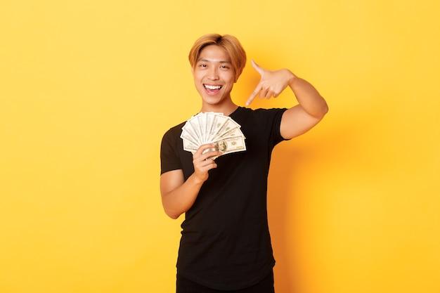 Atrevido e bonito loiro coreano, sorrindo feliz e apontando o dedo para o dinheiro, ganhando dinheiro, parado na parede amarela
