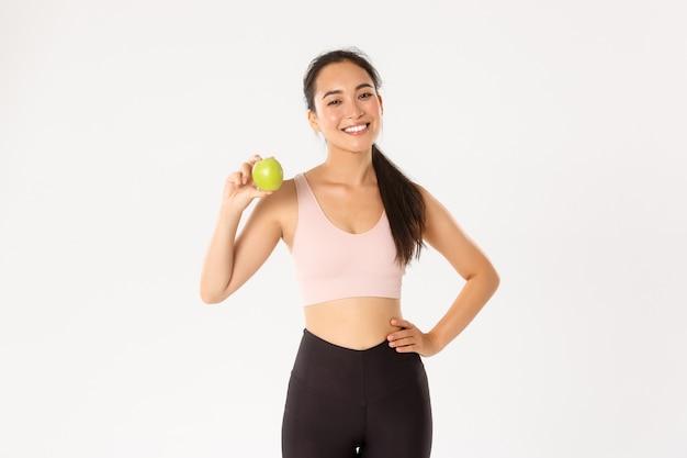 Atrevido instrutor de fitness feminino asiático atraente, instrutor de garota em conselhos sobre activewear, comer alimentos saudáveis após o treino e treino, em pé com a apple.