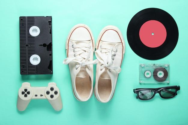Atributos antiquados da cultura pop dos anos 80 no fundo da cor menta. tênis velhos, gamepad, cassete áudio, fita de vídeo, placas de vinil, óculos 3d. minimalismo, vista superior