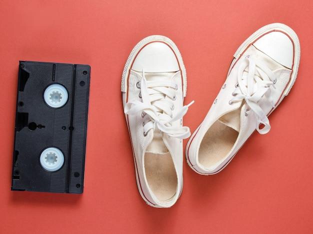 Atributos da cultura pop com tênis branco retrô e videoteipe