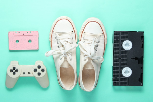 Atributos da cultura pop dos anos 80 em fundo de cor hortelã. tênis velhos, gamepad, cassete de áudio, fita de vídeo. minimalismo, vista superior