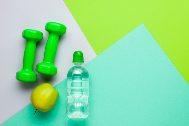 Atributos de esportes plana leigos com garrafa de água e maçã