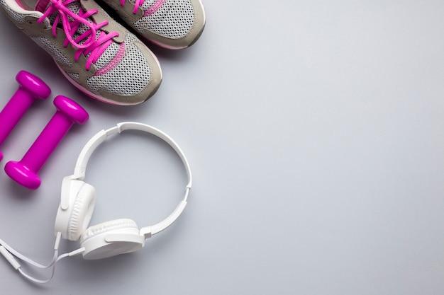 Atributos de esportes rosa vista superior com fones de ouvido